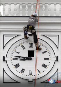 Old clock tower clock repair in progress on a historic church clock face by an onsite technician suspended in the air