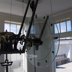 Back of a Glass clock in a museum with gears from a mechanical clock