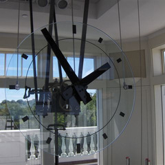 Glass clock with black numbers suspended above a lobby in a museum