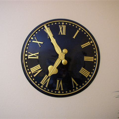 Gold Leaf Roman numerals on a gloss black stainless steel wall clock