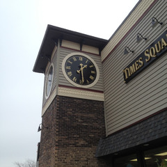 Raised gold leaf numbers on a black clock face, Crete IL