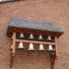 Bronze bell chimes on a church wall